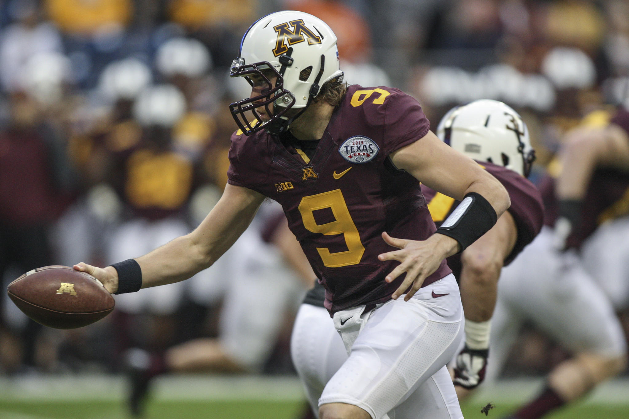 Minnesota quarterback Philip Nelson hands the ball off during the first quarter of the Texas Bowl against Syracuse.
