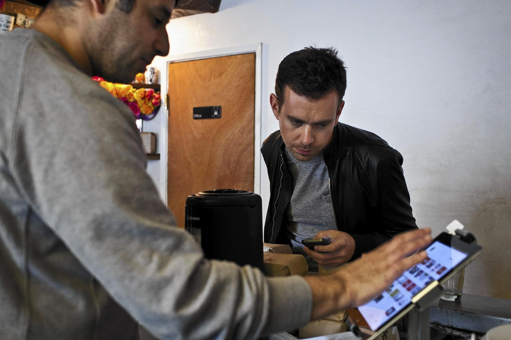 Square Chief Executive Jack Dorsey, right, uses his company's mobile payment tool at a cafe in San Francisco in 2012.