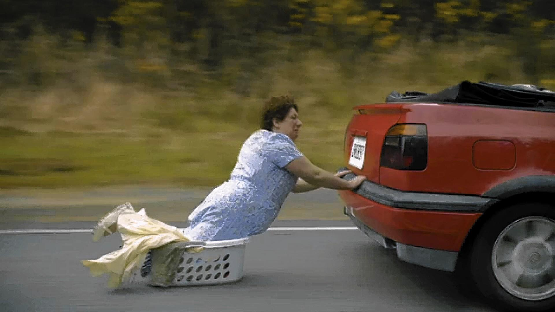 """A mother hangs onto the bumper of the car with her son and his girlfriend in an Old Spice """"Smellcome to Manhood"""" TV ad."""
