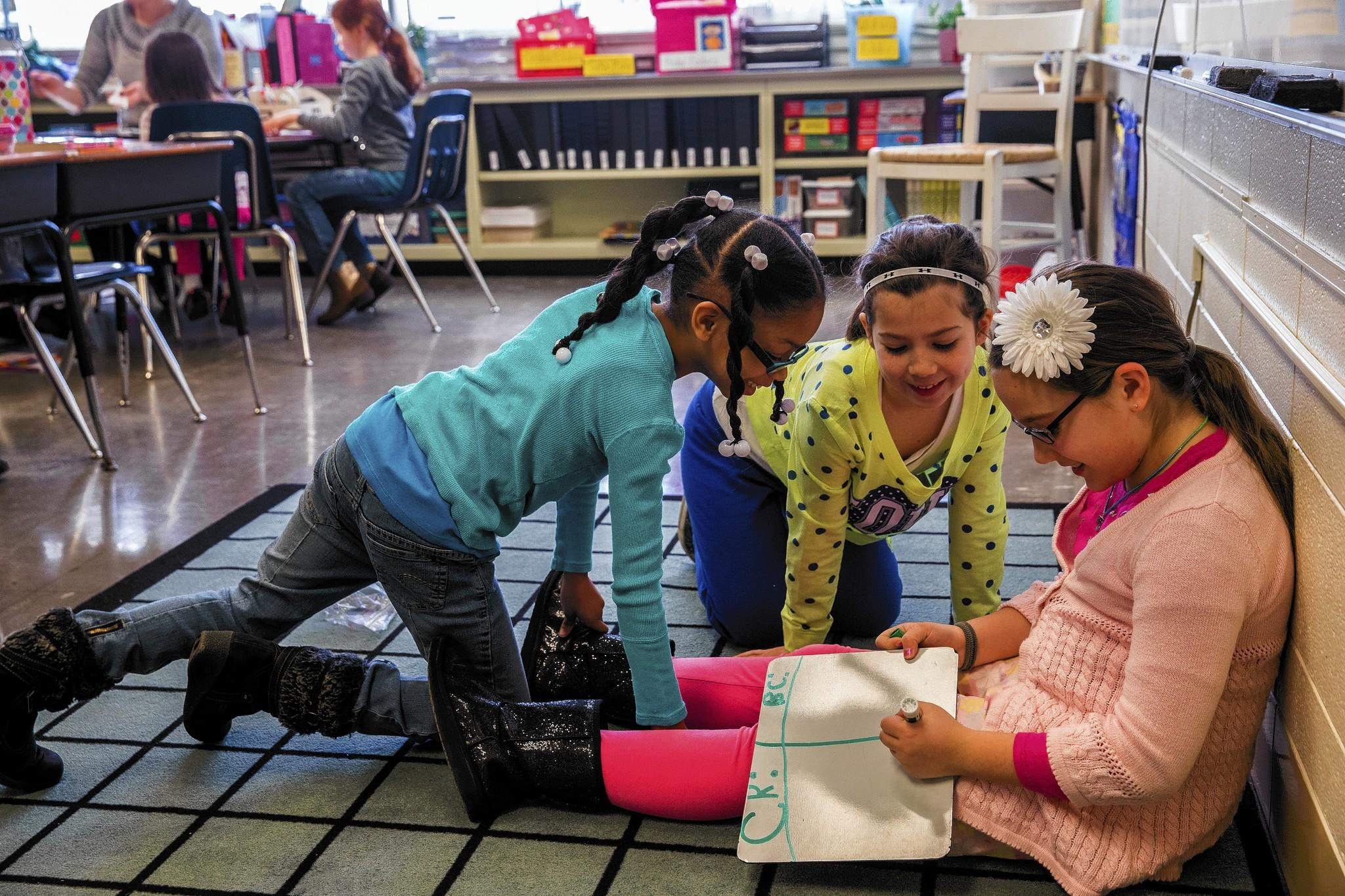 Third-graders Cashana King, from left, Brooklyn Carroll and Abigail McCune work during math class to prepare for a field test of a new state exam at Troy Shorewood Elementary School in Shorewood on Wednesday.