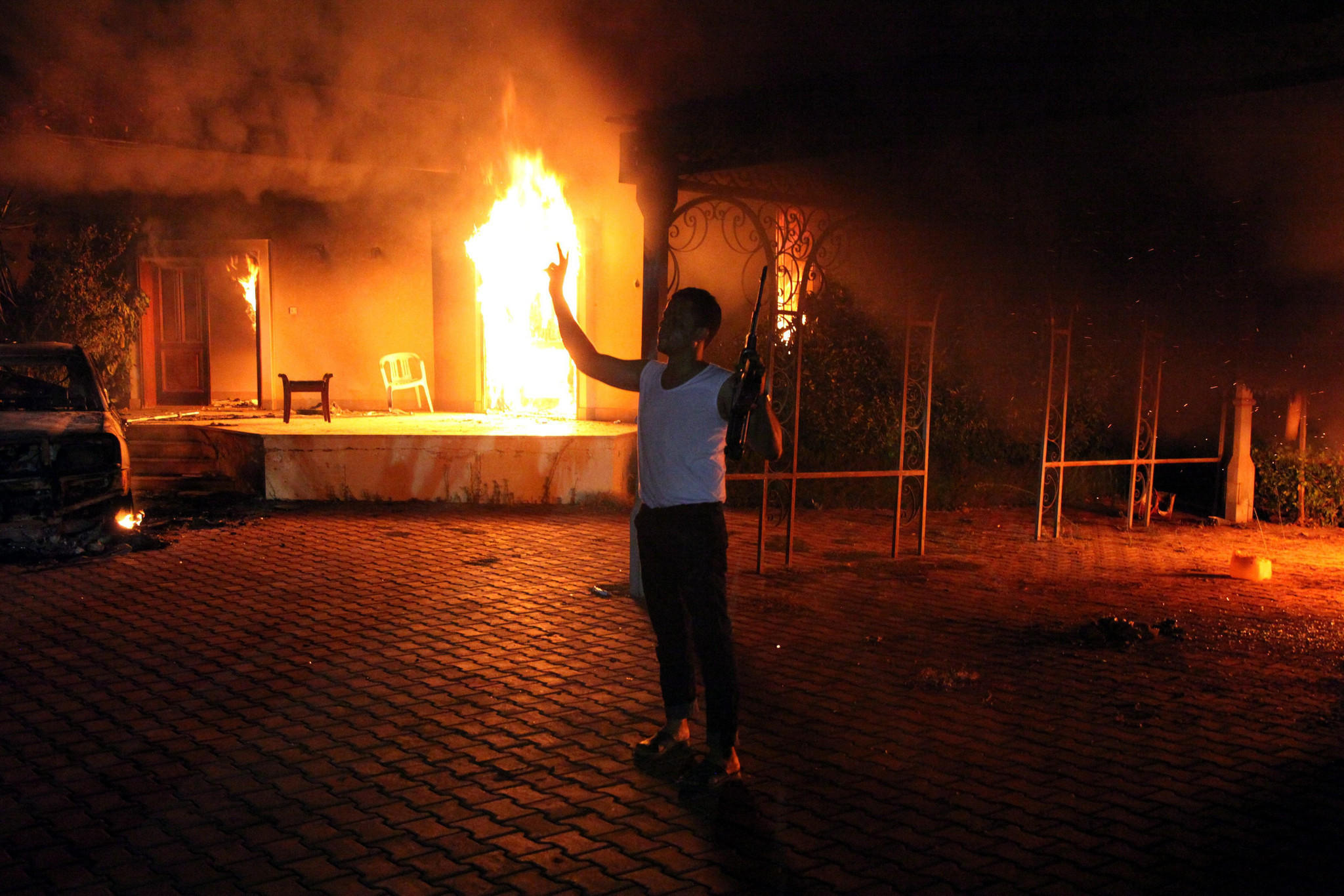 An armed man holds his rifle as he stands next to blazing buildings at the U.S. Consulate in Benghazi in September 2012. The U.S. ambassador to Libya, Chris Stevens, and three others were killed when armed attackers stormed the consulate.