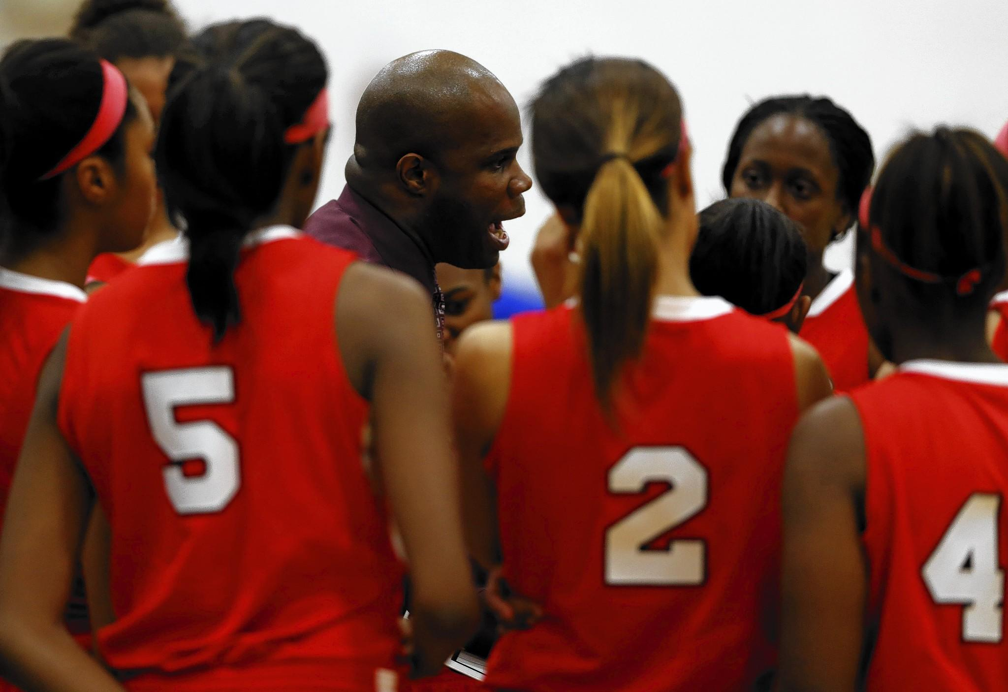 Homewood-Flossmoor girls varsity basketball coach Anthony Smith speaks to his players Thursday during a game against Sandburg High School in Orland Park.