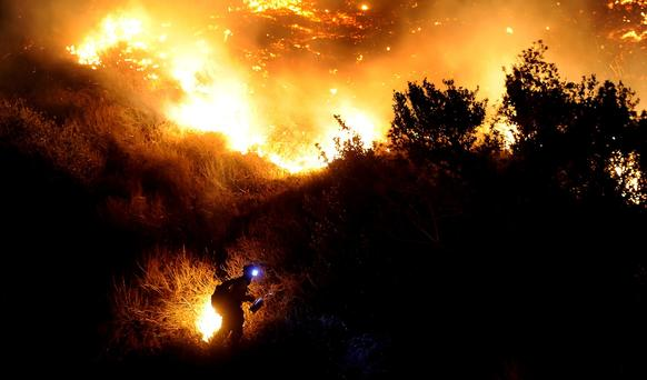A firefighter starts a backfire along San Gabriel Canyon Road in Azusa as the Colby fire burns through brush Thursday night.