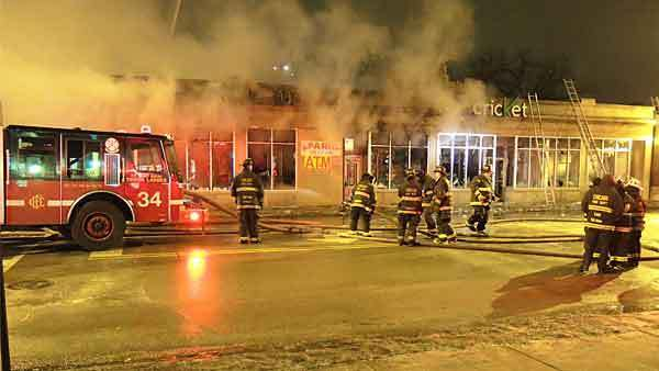 Firefighters on the scene of an early morning fire at the corner of South Martin Luther King, Jr. Drive and East 75th Street.