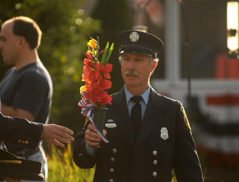 Manchester firefighter Hatch Odell carries flowers to be placed near one of two tablets listing the names of the 343 New York firefighters who lost their lives on 9/11. He did this shortly before the Town of Manchester's event marking the 10th anniversary of 9/11.