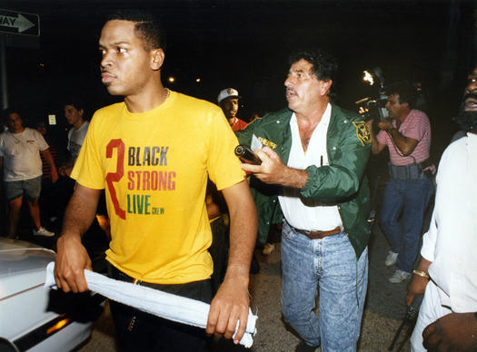 6/10/90--Luther Campbell, with towel, is led away by Broward Sheriff's Officer on Hollywood Boulevard. He is a member of 2 Live Crew.
