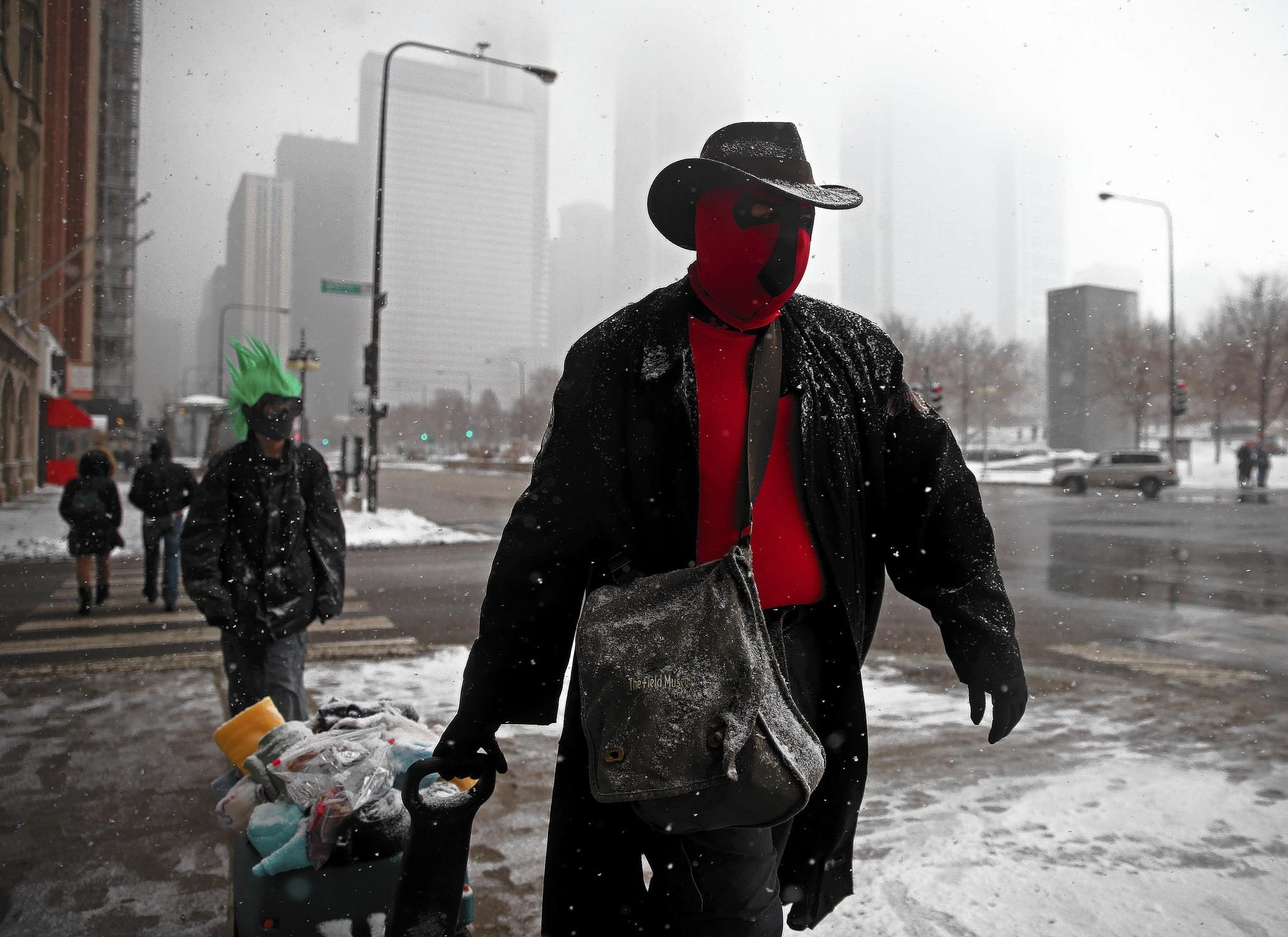 Crusader Prime, right, and The Variable walk Michigan Avenue to deliver food and blankets to the homeless in downtown Chicago.