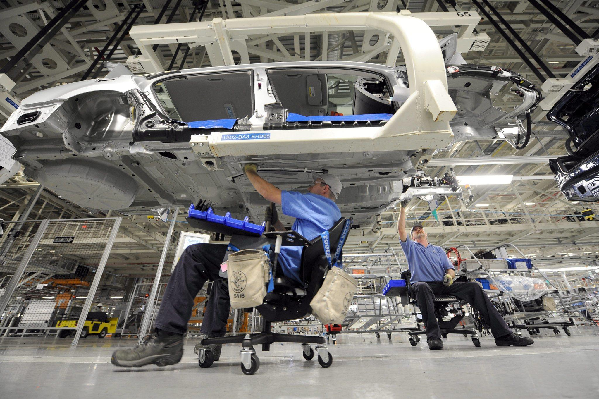 Employees work on the underside of a Passat sedan at the Volkswagen automobile assembly plant in Chattanooga, Tenn.