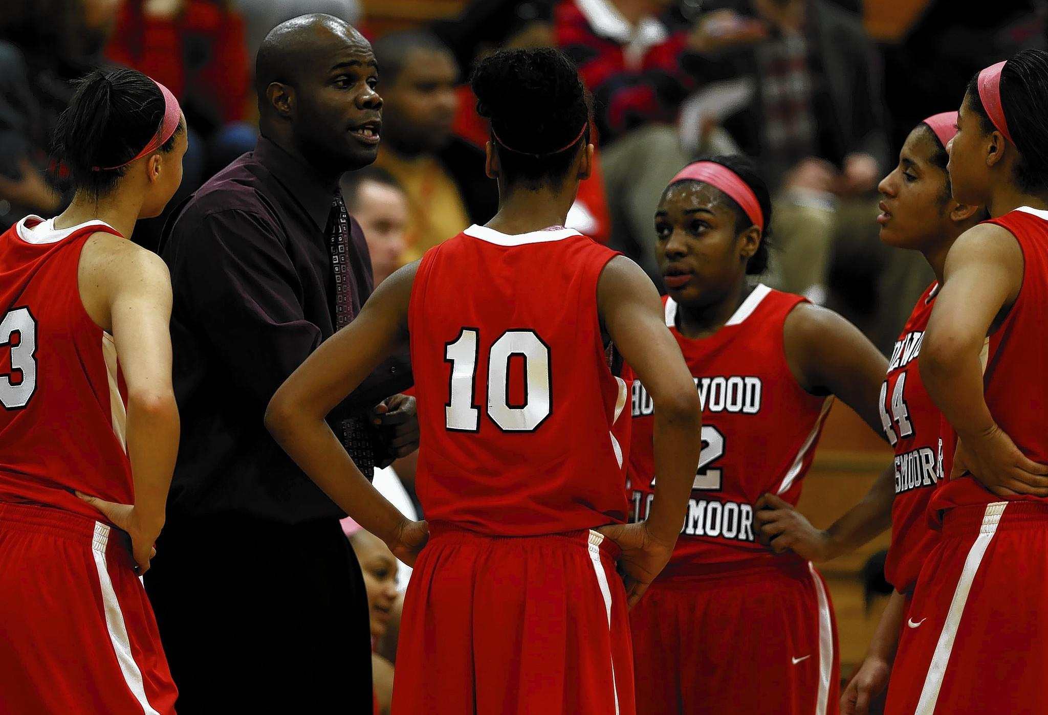 A lawsuit filed against Homewood-Flossmoor High School alleges girls basketball coach Anthony Smith, second from left, recruited six players from other districts — including four from his former school, Bolingbrook, which he left last year.