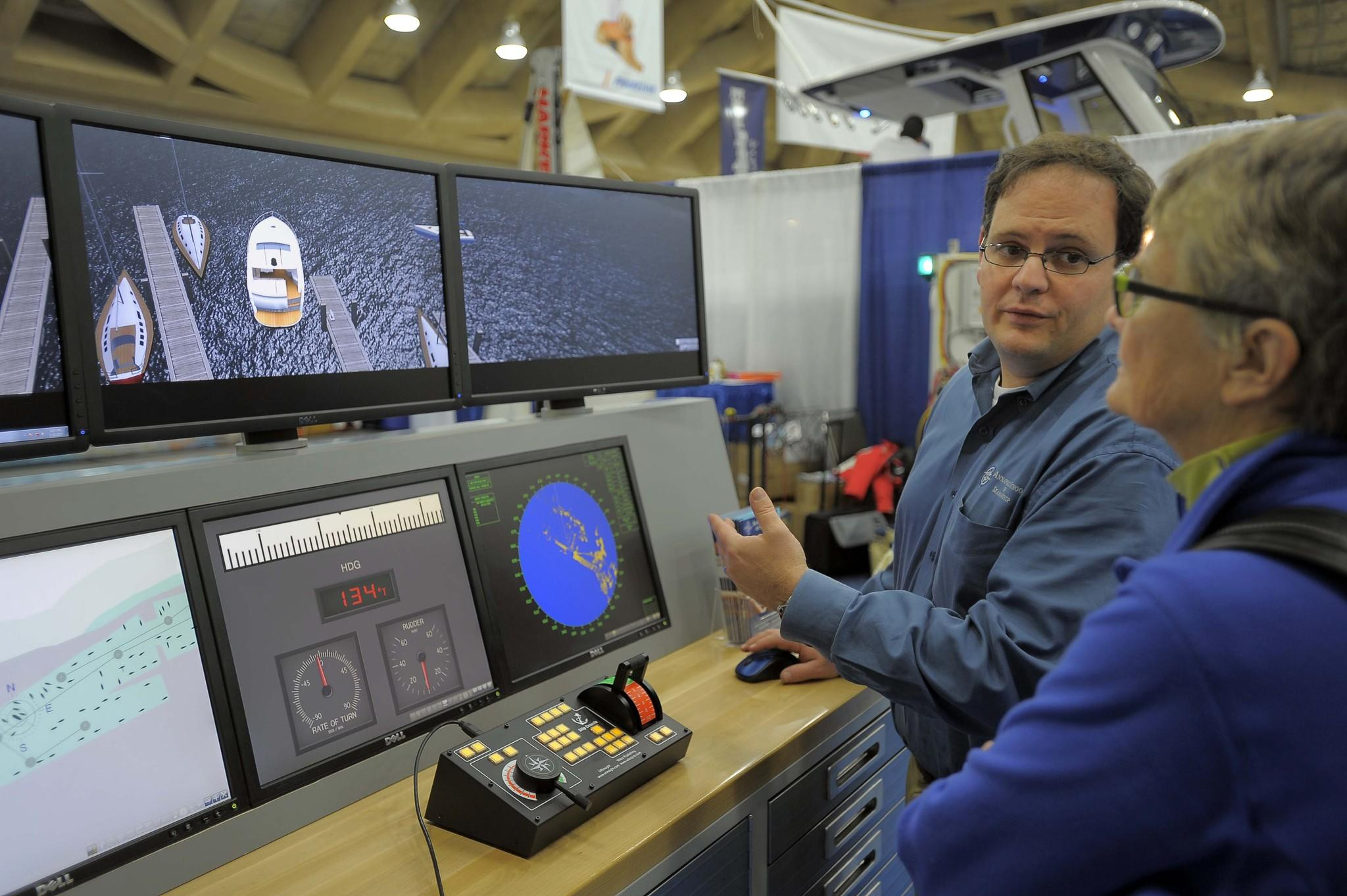 Capt. John Martino, founder and president of the Annapolis School of Seamanship, shows an alternate view of a Coast Guard vessel to Jody Schroath of Annapolis at the Baltimore Convention Center in 2012.