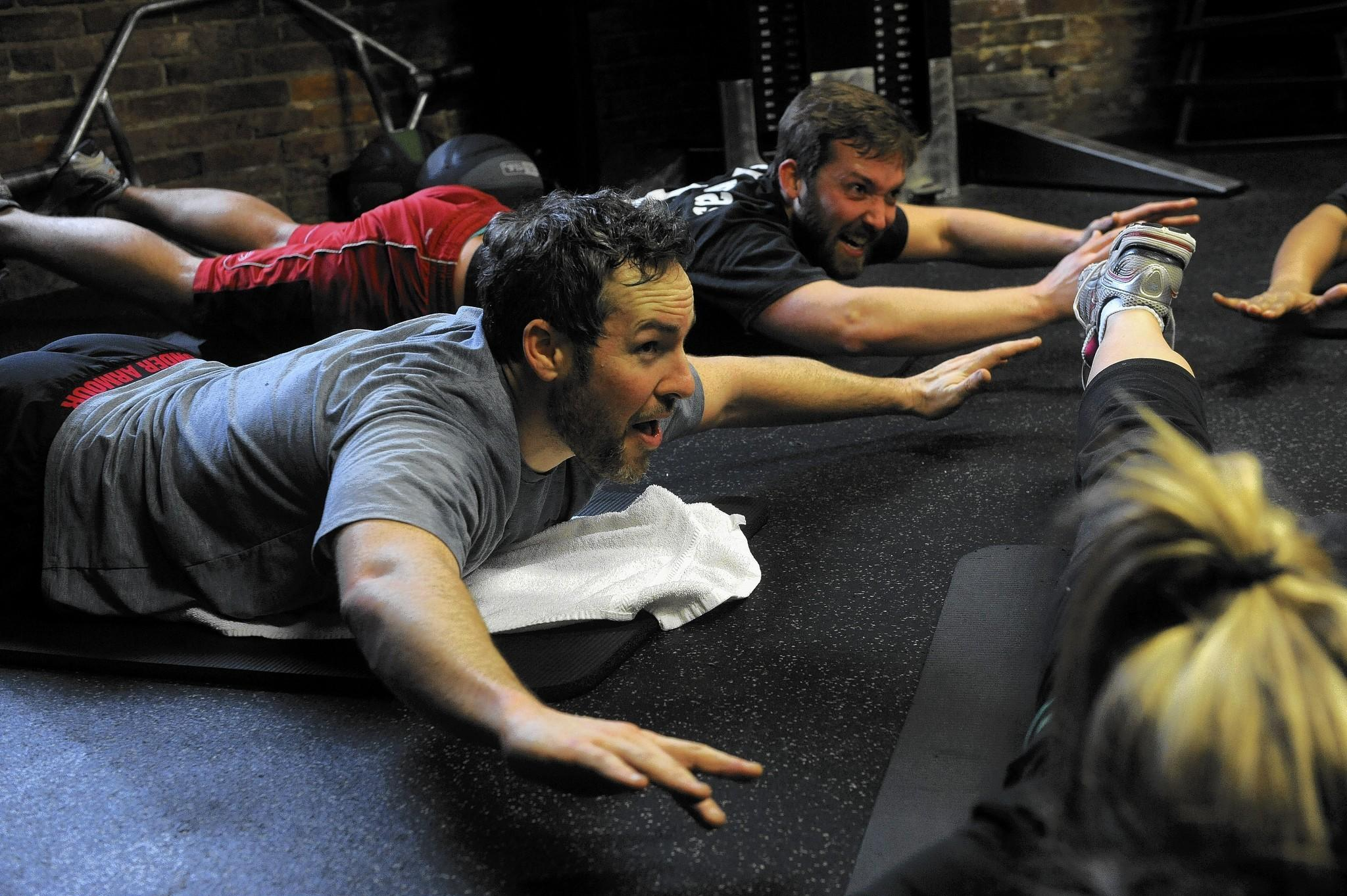 Jared Kelly (left), director of marketing, and Woody Heffern, marketing, Agora Inc. work their core with a Superman exercise. They join other employees to enjoy a midday workout at the company gym. This session, Agora Employee Fitness by FX Studios, is lead by Heather Hatfield, an FX personal trainer.