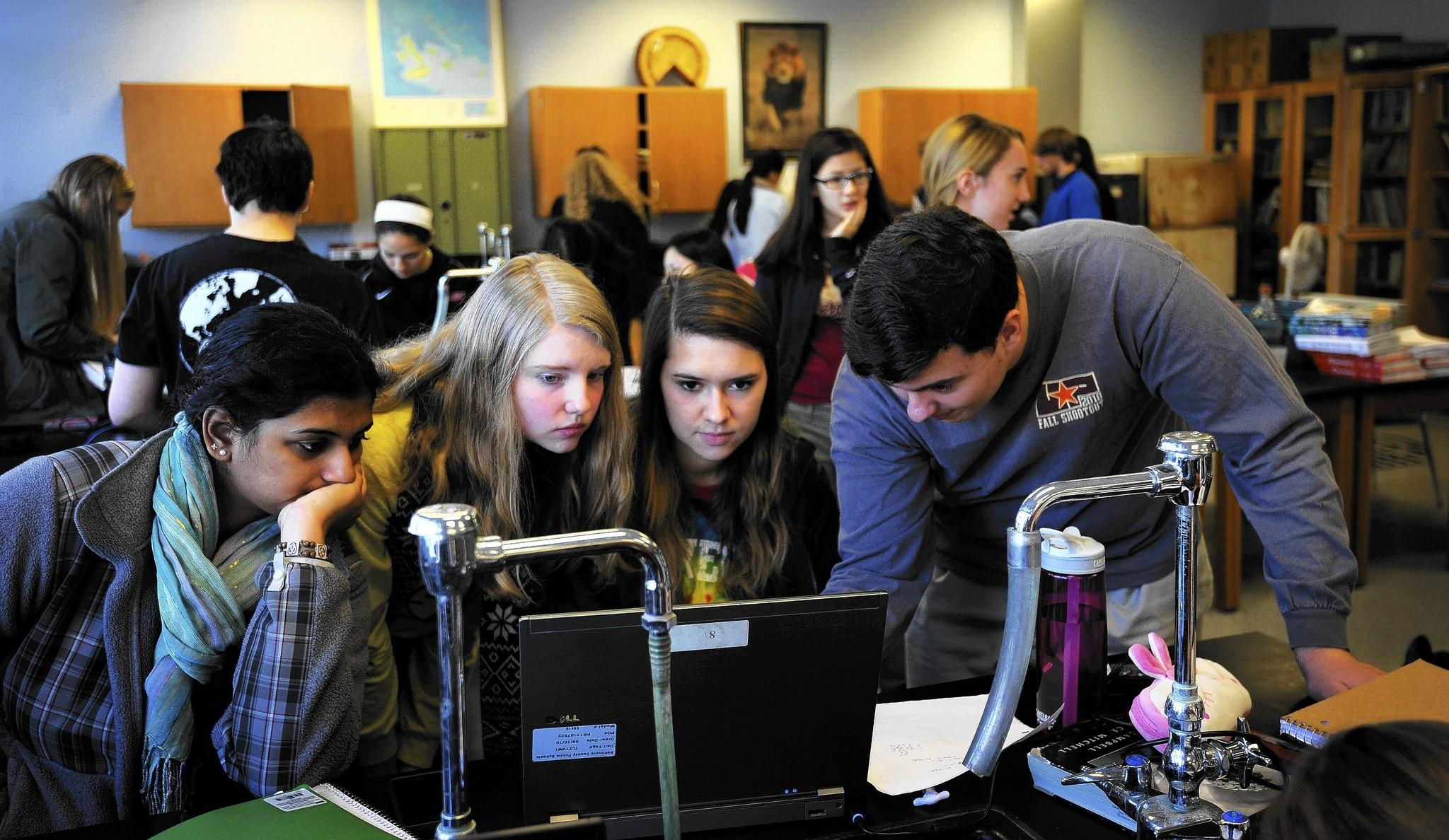Dulaney High School AP biology students gather around a laptop as they work in class.