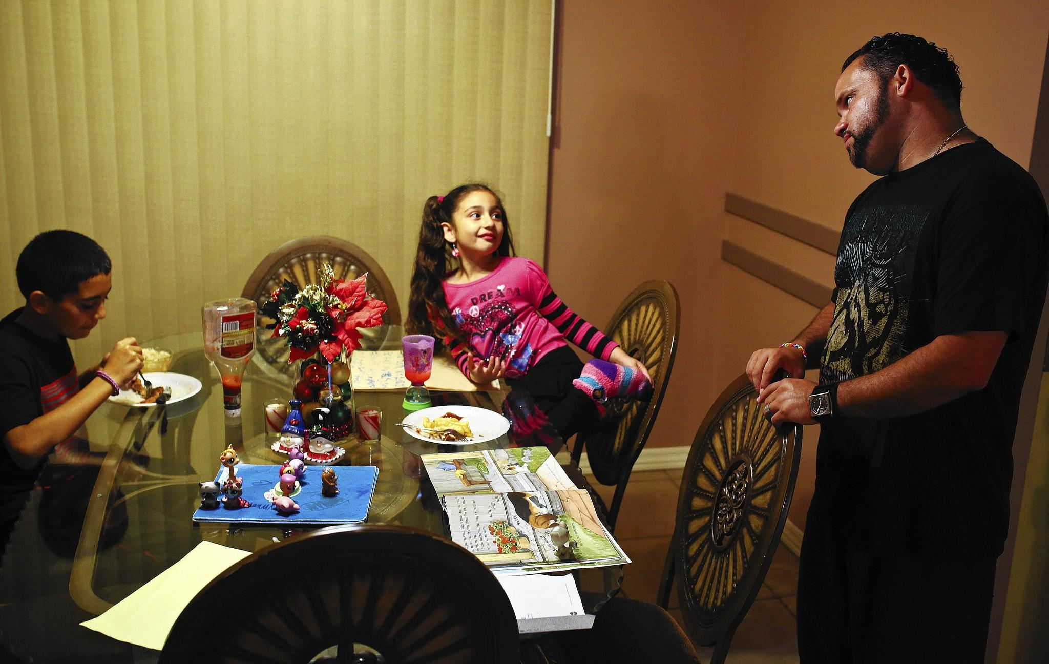 Jose Mendez spends time with his daughter Ariella Mendez and son Pablo DeLeon after cooking them dinner at their Deltona home on January 9, 2014. Mendez is a stay-at-home dad and Army Reservist who is raising up to five kids at any one time.