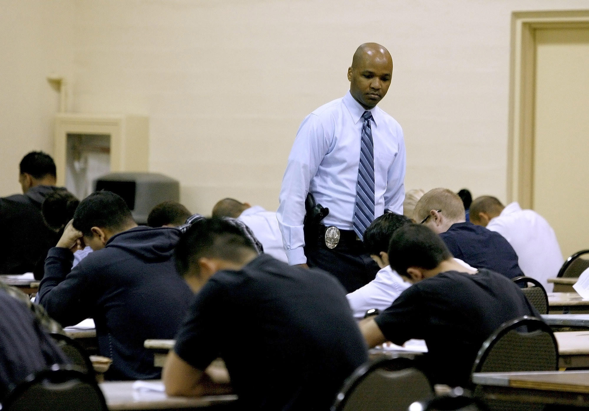 Glendale Police Detective Victor Jackson keeps an eye on applicants taking the police officer recruit written exam at the Glendale Civic Auditorium in Glendale on Thursday, Nov. 1, 2012.