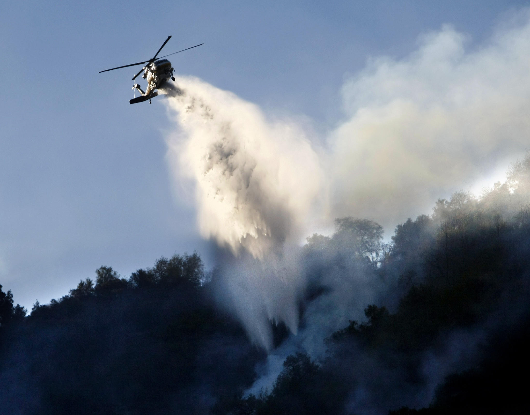 A helicopter drops water on spot fires on a smoky morning on day two of the Colby fire in the Angeles National Forest north of Azusa on Friday, January 17, 2014.