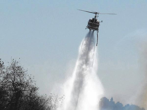 The Orange County Fire Authority helicopter drops water on a small brush fire in Talbert Regional Park on Thursday.