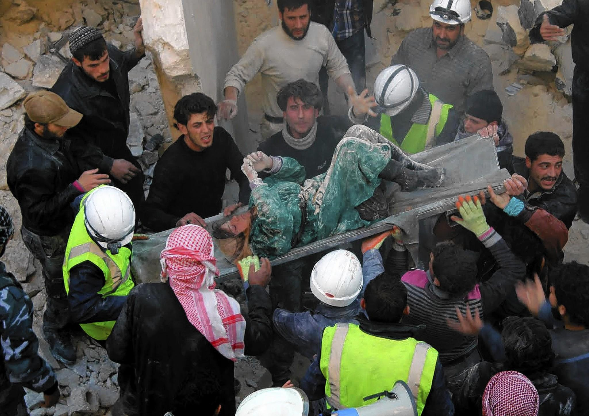 The body of a woman is carried out of the rubble in the northern Syrian city of Aleppo on Saturday as people search for survivors after airstrikes by Syrian forces.