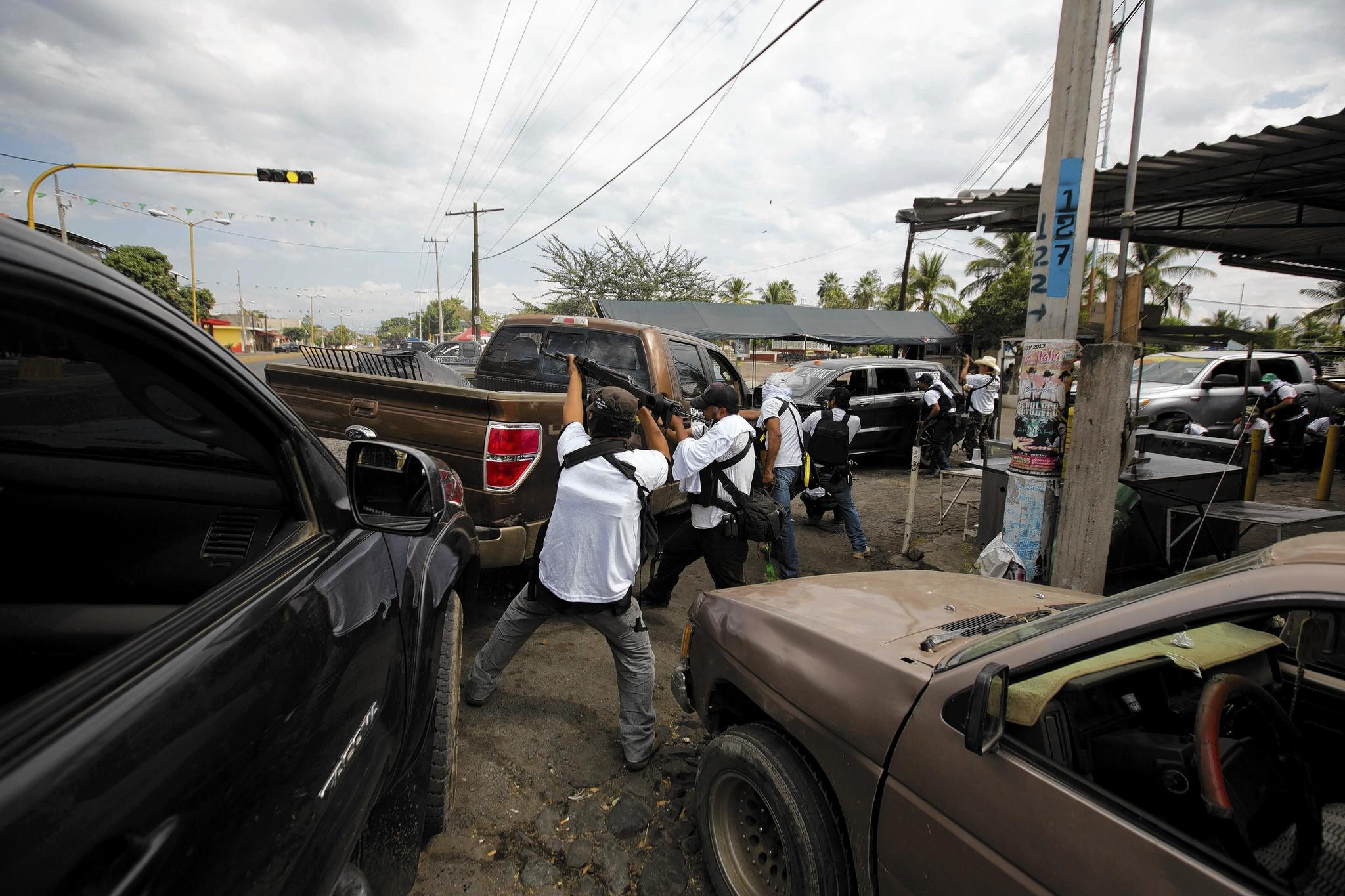 """Self-defense"" militia fighters engage in a battle with suspected Knights Templar drug cartel members in Nueva Italia, Mexico. The vigilantes, now backed by federal police, have taken control of the town."