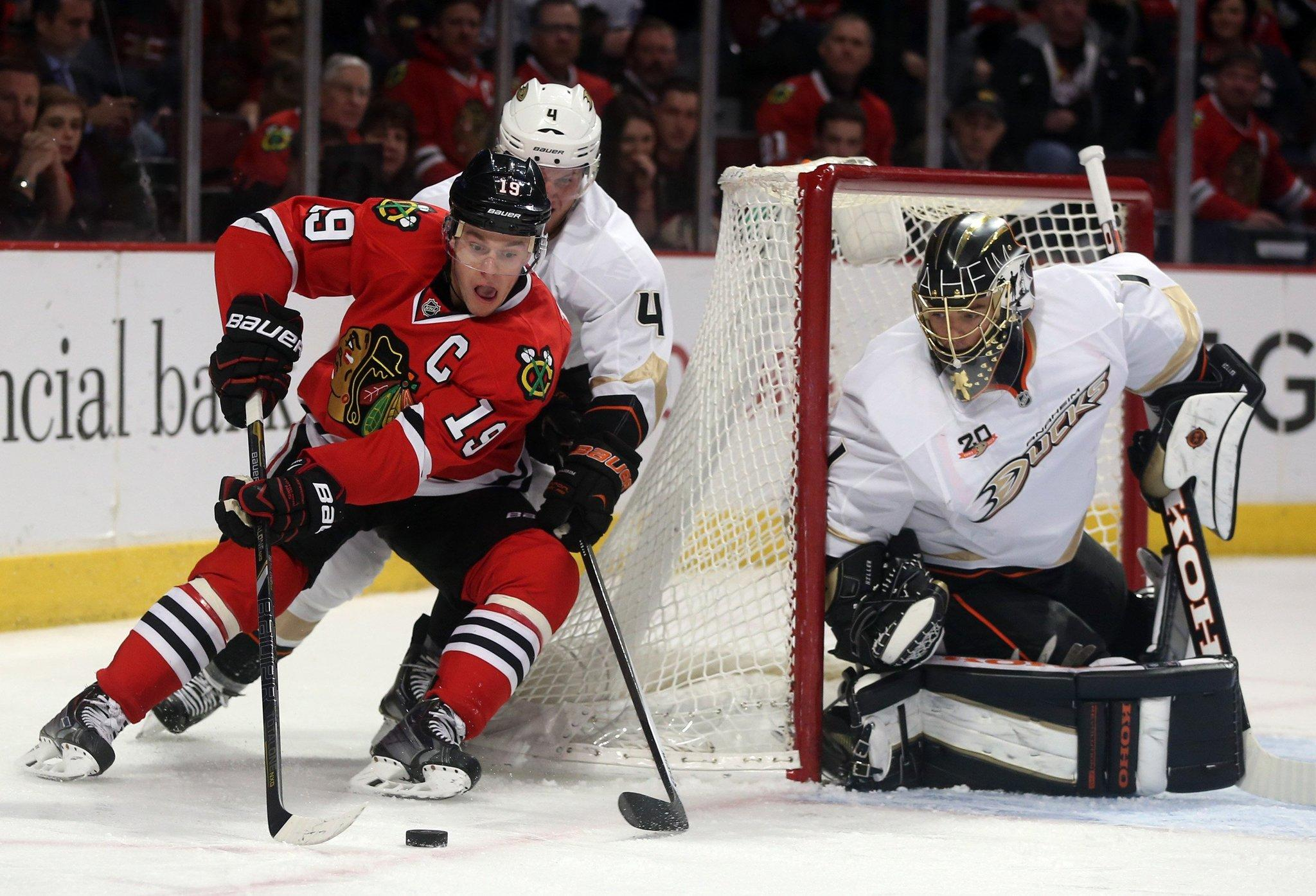 The Anaheim Ducks' Cam Fowler (4) defends against the Chicago Blackhawks' Jonathan Toews (19) as Anaheim Ducks goalie Jonas Hiller (1) holds the post in the first period on Friday, Jan. 17, 2014, at the United Center in Chicago.