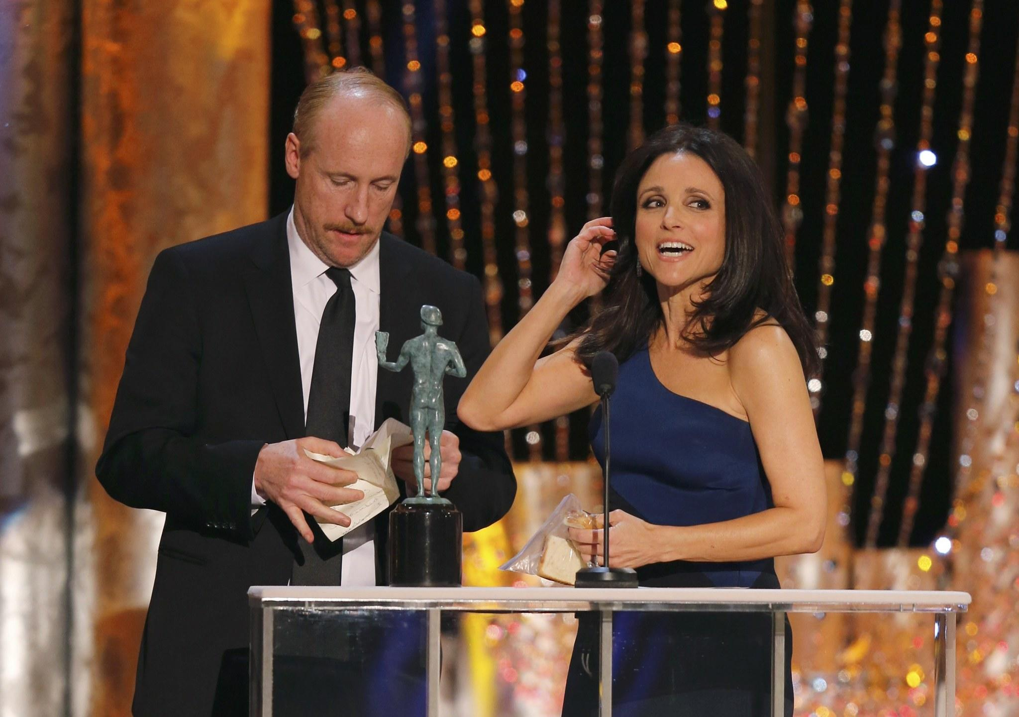 "Julia Louis-Dreyfus accepts the award for Outstanding Performance by a Female Actor in a Comedy Series for ""Veep"" as co-star Matt Walsh helps with her speech at the 20th annual Screen Actors Guild Awards in Los Angeles, California January 18, 2014."