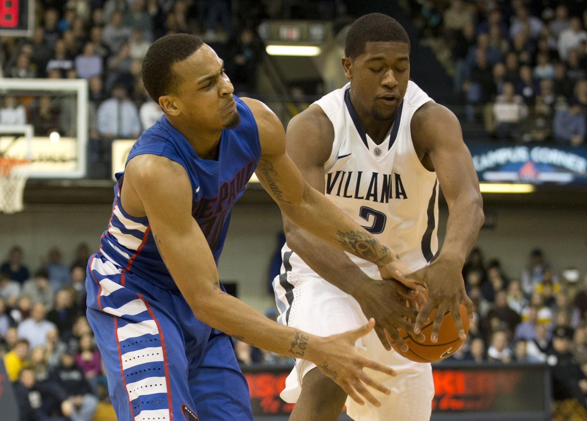 Guard Brandon Young (left)of the DePaul Blue Demons and forward Kris Jenkins of Villanova Wildcats both reach for the ball.