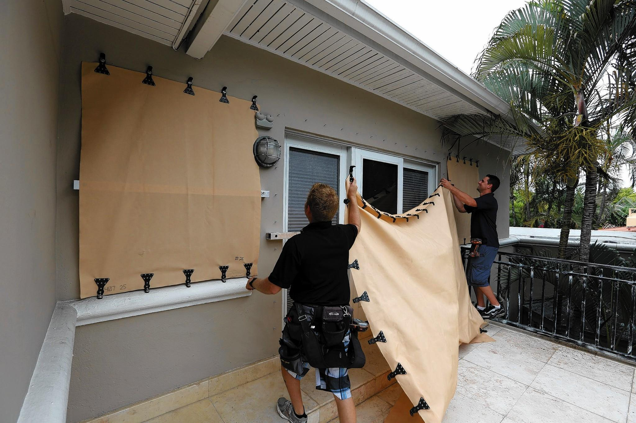 Brandon Susich, right, and Albert Petrello install fabric storm shutters on a home in Miami Beach, Florida, on June 1, 2013.