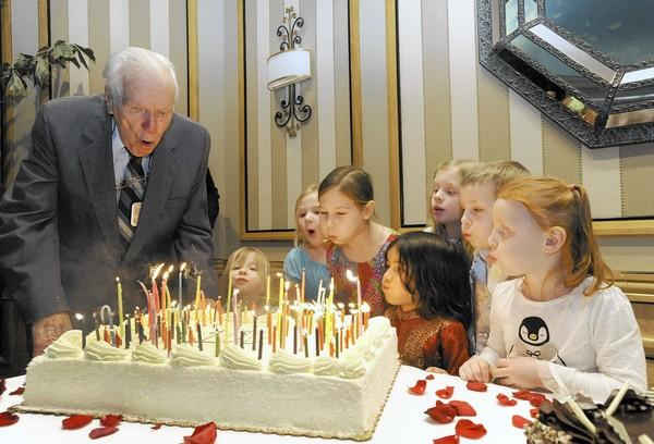 """John """"Captain Jack"""" Slaughter, a retired Navy captain, blows out 100 candles with the help of some of his 11 great-grandchildren during his 100th birthday party on Sunday, Jan. 19, at The Colonnade, where he lives with his wife, Bess, 97."""