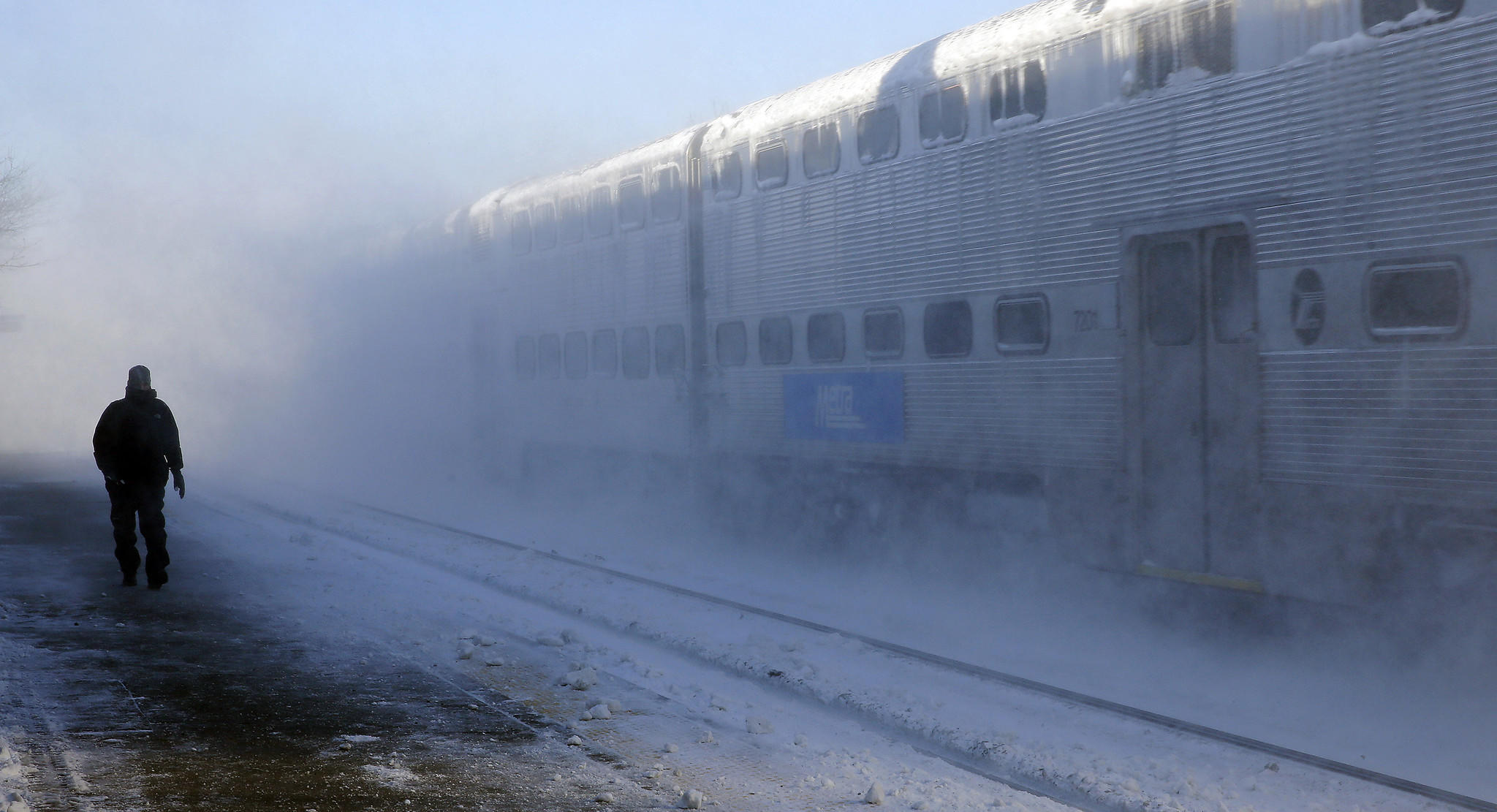 An express Metra train creates a cloud of snow as it passes the La Grange Road station on Monday.