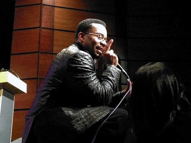 Radio show host Lonnie Hunter kneels on the stage to talk to guests at a Martin Luther King Jr. gospel concert in Newport News on Sunday.