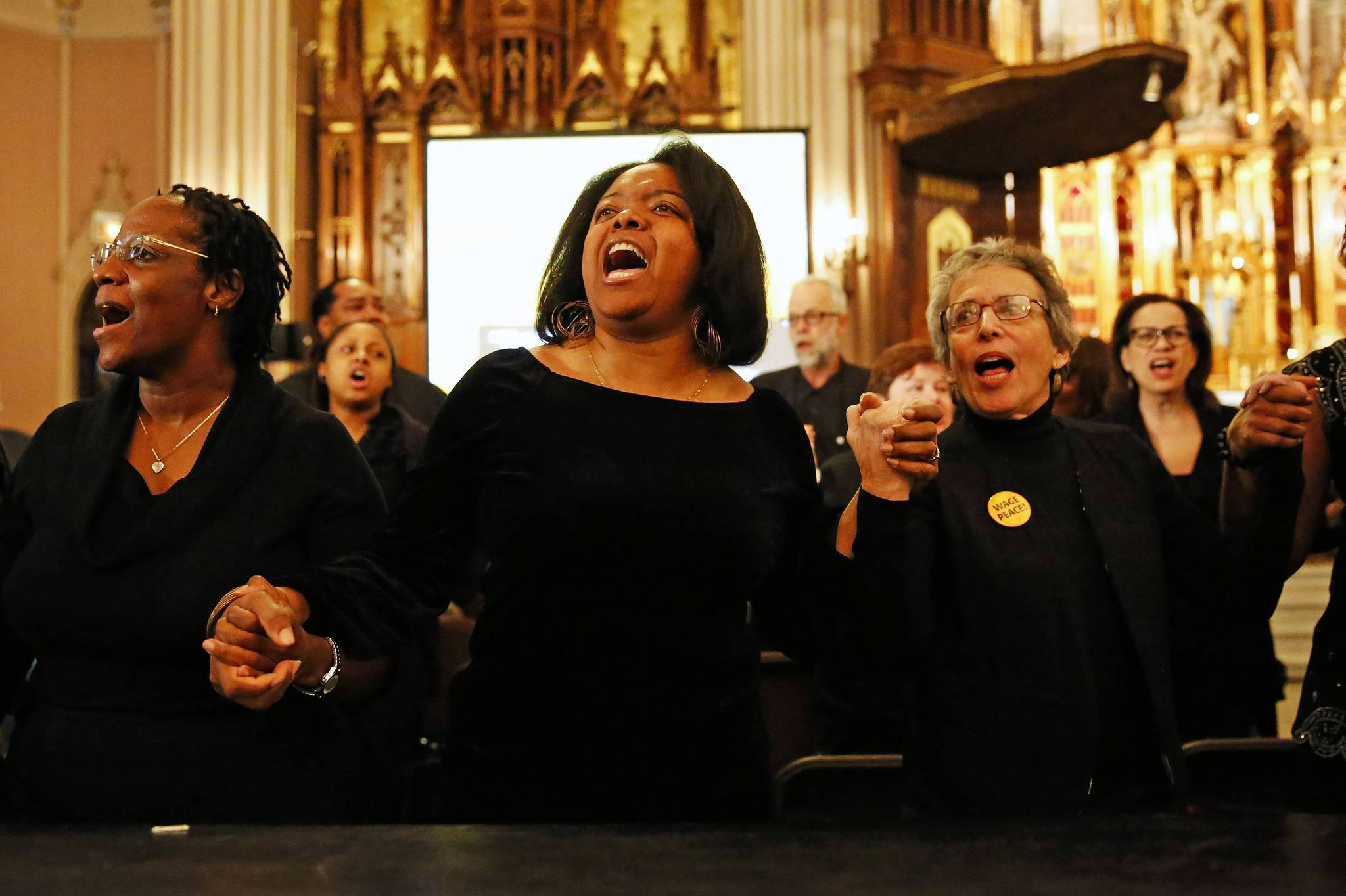 "A choir sings ""We Shall Overcome"" at St. Michael the Archangel Catholic Church on Sunday."