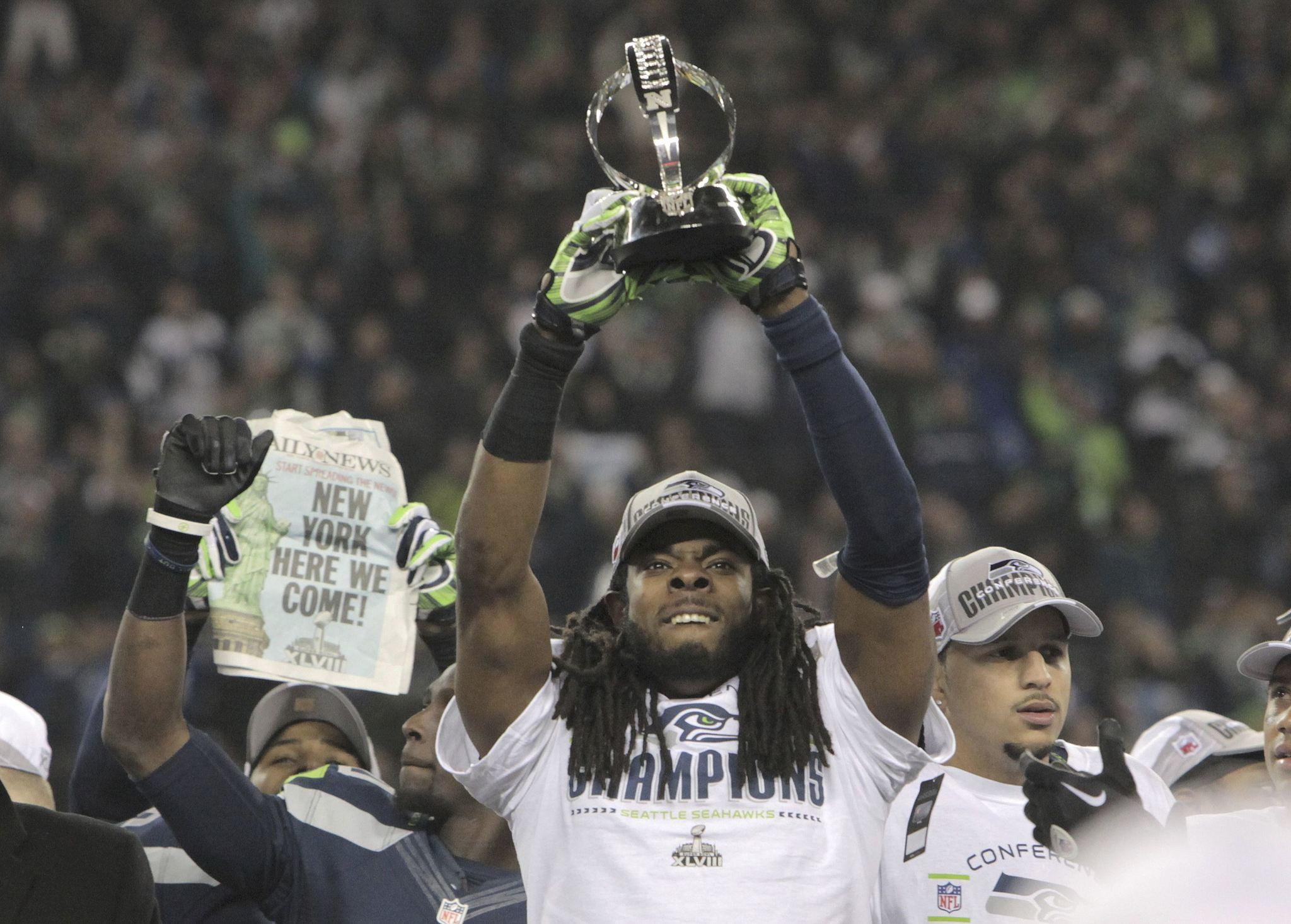 The Seahawks' Richard Sherman holds up the George Halas Trophy after they defeated the San Francisco 49ers in the NFC Championship game.