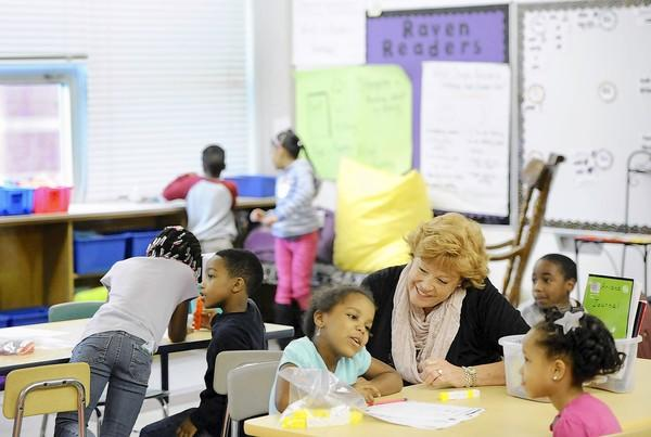First-grade paraeducator Susan Dumler works on a math lesson with Emari Smith, center, and Ariana Henderson, right, at Halstead Academy in Parkville on Oct. 11.