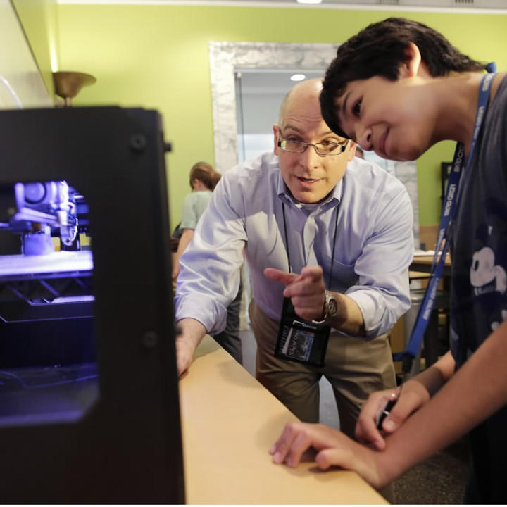Mark Andersen, The Chicago Public Library's Division Chief of Business, Science & Technology, shows Abraham Valle, 13, one of three MakerBot Replicator 3D printers at the Harold Washington Library's Maker Lab, July 8, 2013.