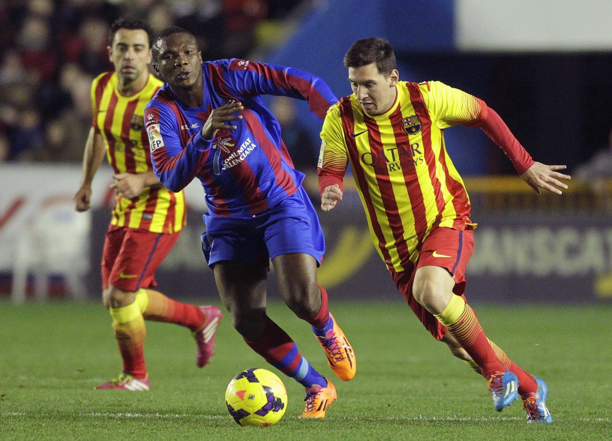 Barcelona's Lionel Messi (R) and Levante's Simao Junior fight for the ball, as Barcelona's Xavi Hernandez watches, during their Spanish First Division soccer match at the Ciudad de Valencia stadium in Valencia, January 19, 2014.