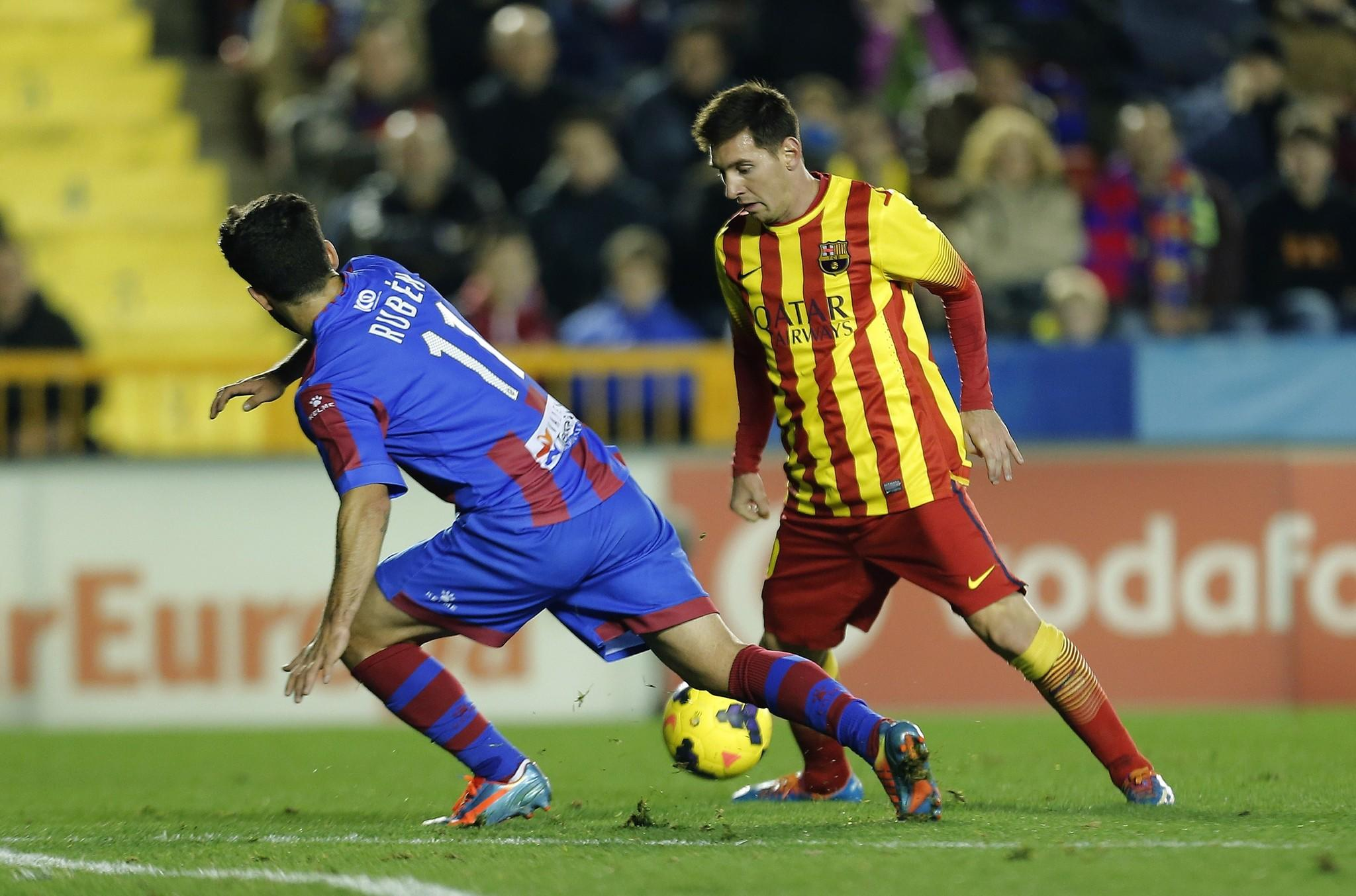 Levante's midfielder Ruben Garcia (L) vies with Barcelona's Argentinian forward Lionel Messi during the Spanish league football match Levante vs Barcelona at the Ciutat de Valencia Stadium in Valencia on January 19, 2014.