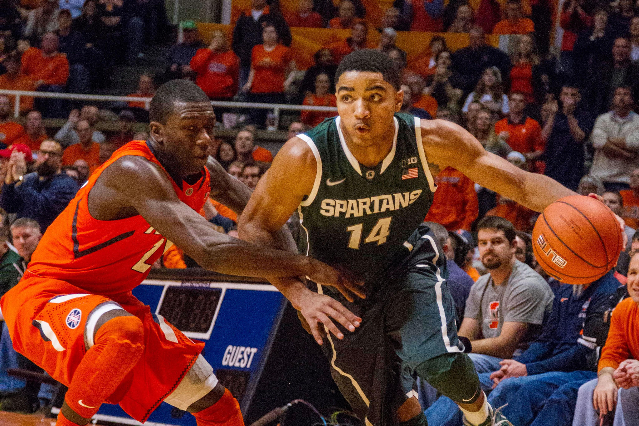 Michigan State Spartans guard Gary Harris (14) dribbles the ball around Illinois Fighting Illini guard Kendrick Nunn (25) in the second half of the game at State Farm Center.