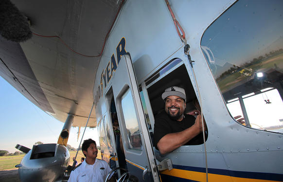 "Rapper Ice Cube, right, takes a seat in the Goodyear Blimp at the airship's base in Carson. Youths from ""A Place Called Home"" got a ride on the blimp at an event where the rapper was on hand to offer donations to the charity."