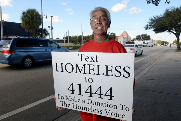 Homeless Voice's Artie Goncalves holds a sign asking motorists to text a donation Monday afternoon outside of the Homeless Voice headquarters in Hollywood.
