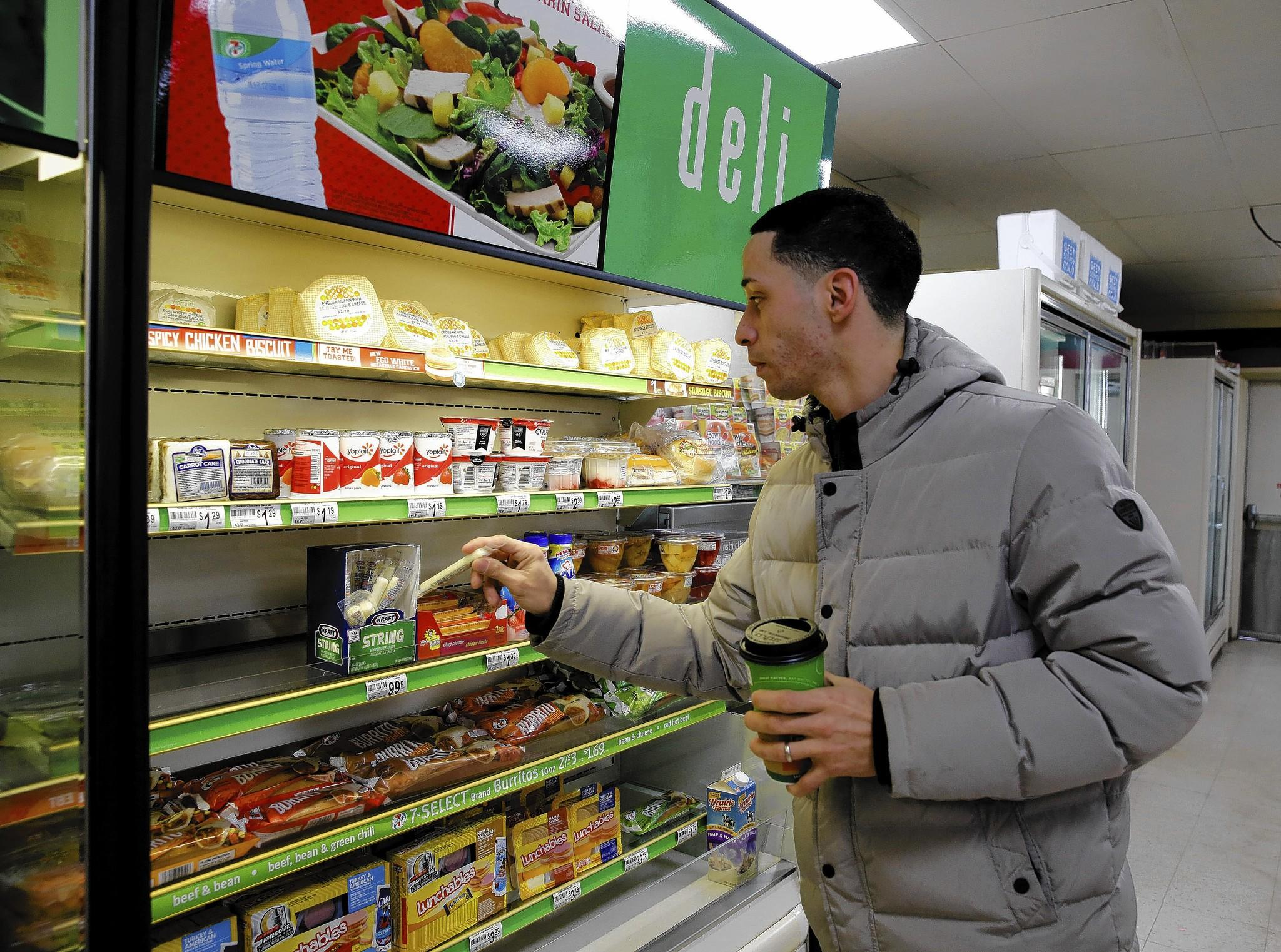 A customer selects string cheese to go with his coffee last week at a 7-Eleven on Fullerton Avenue. The world's largest convenience store chain is increasing its fresh food offerings, including a push toward more healthy snacks.