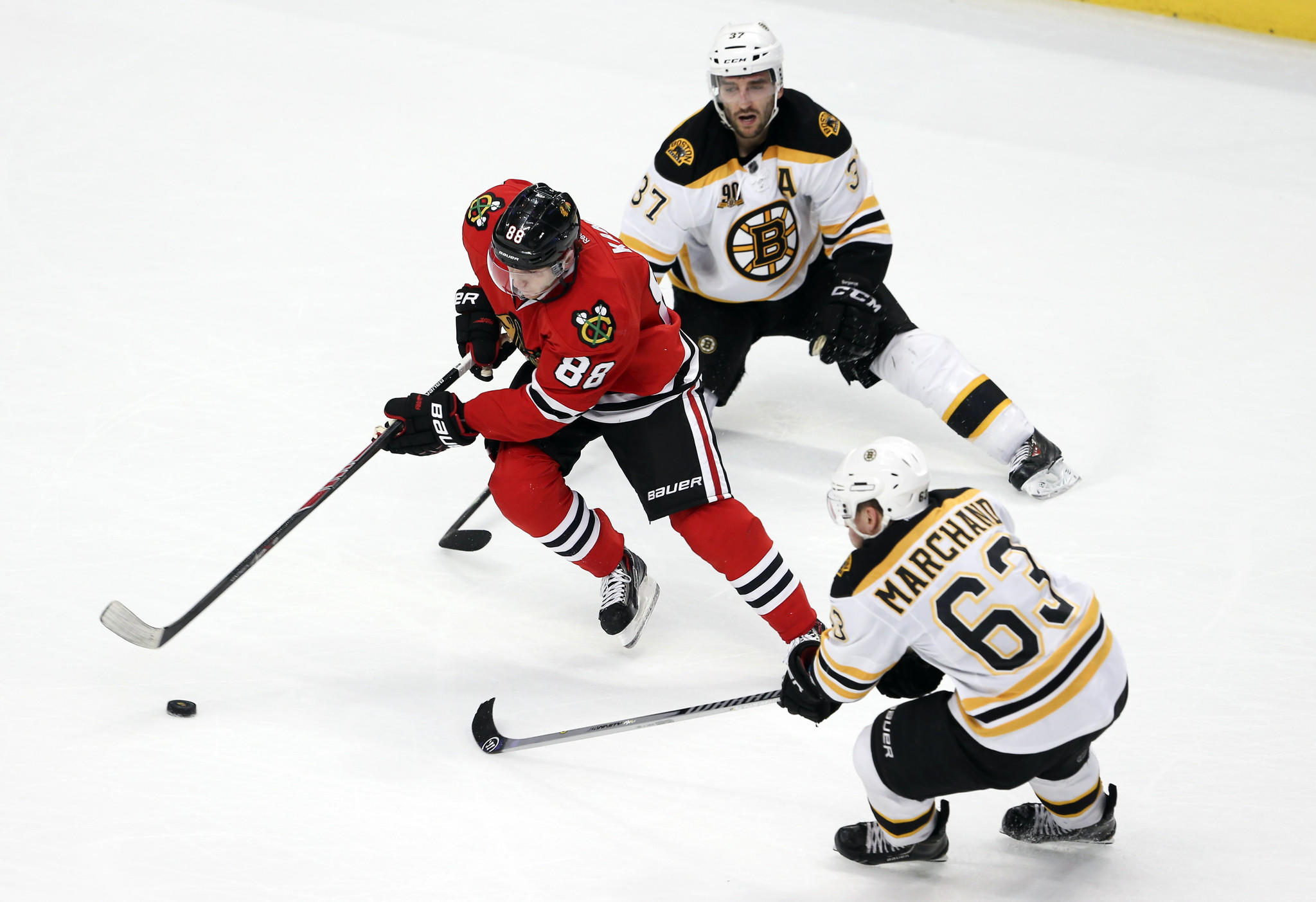 Chicago Blackhawks right wing Patrick Kane (88), maneuvers between Boston Bruins center Patrice Bergeron (37), and Boston Bruins left wing Brad Marchand (63), during the overtime period of their game at the United Center.