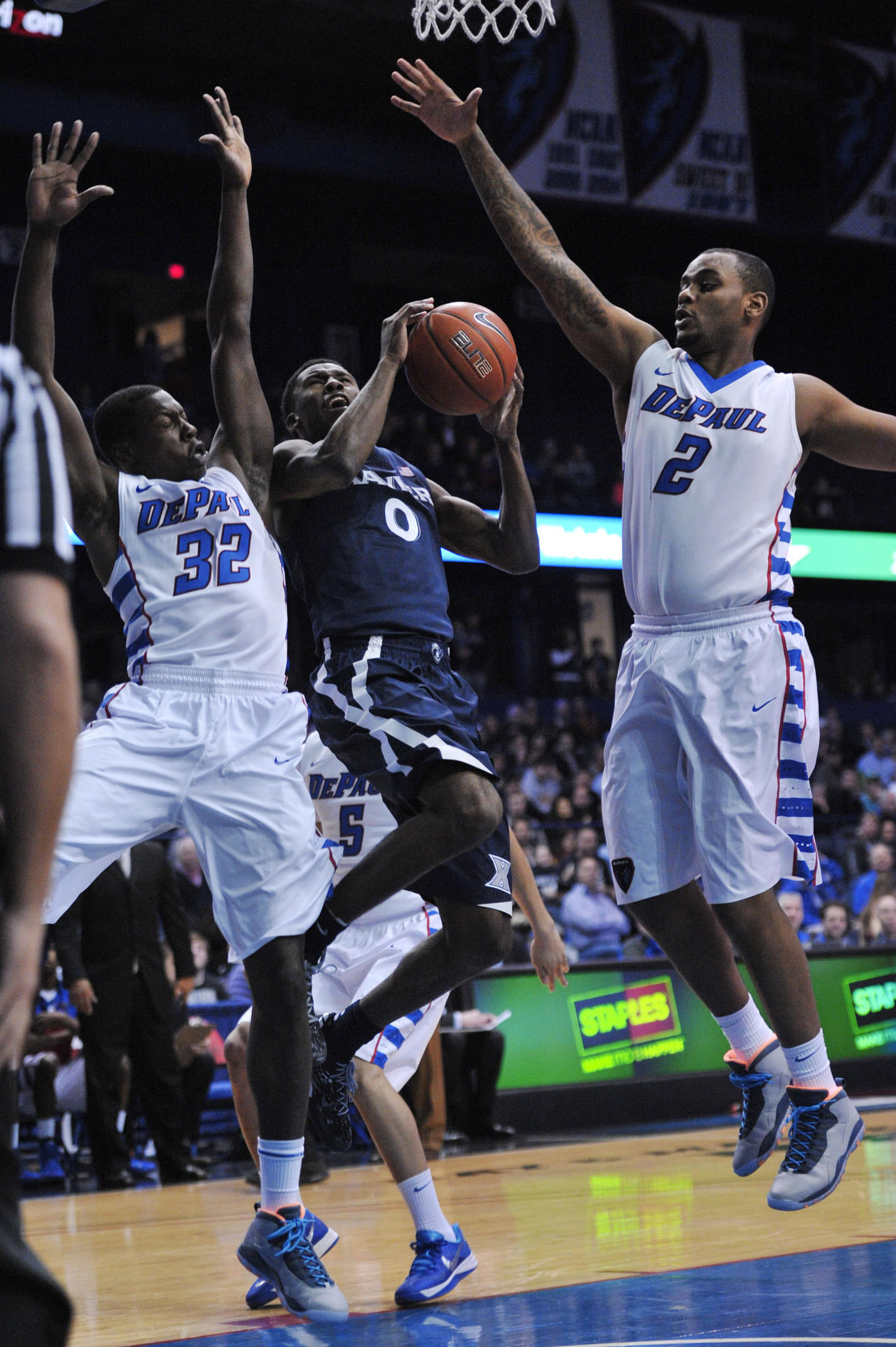 Xavier Musketeers guard Semaj Christon (0) goes to the basket against DePaul Blue Demons center Tommy Hamilton IV (2) and guard Charles McKinney (32).