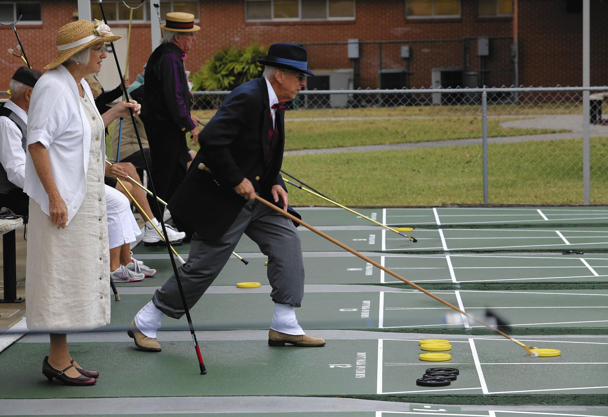 Shuffleboard players dress in vintage clothing to celebrate the 100-year anniversary of the game, during a tournament hosted by the Tavares Shuffleboard Club on Friday, December 27, 2013.