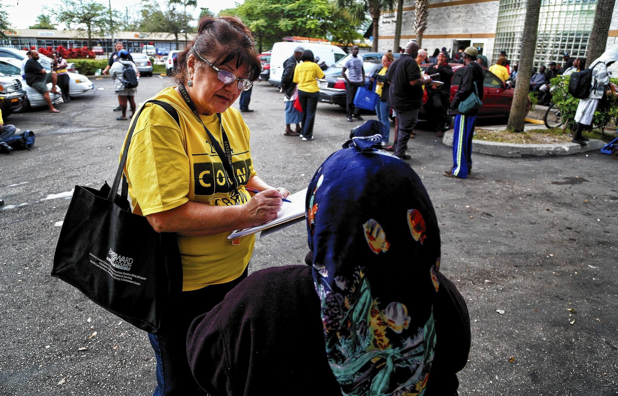 Diane Nickum, a volunteer with the Homeless Point-In-Time County Survey takes information from a homeless woman. Multiple Broward agencies are joining forces in an effort to get the homeless housing placement.
