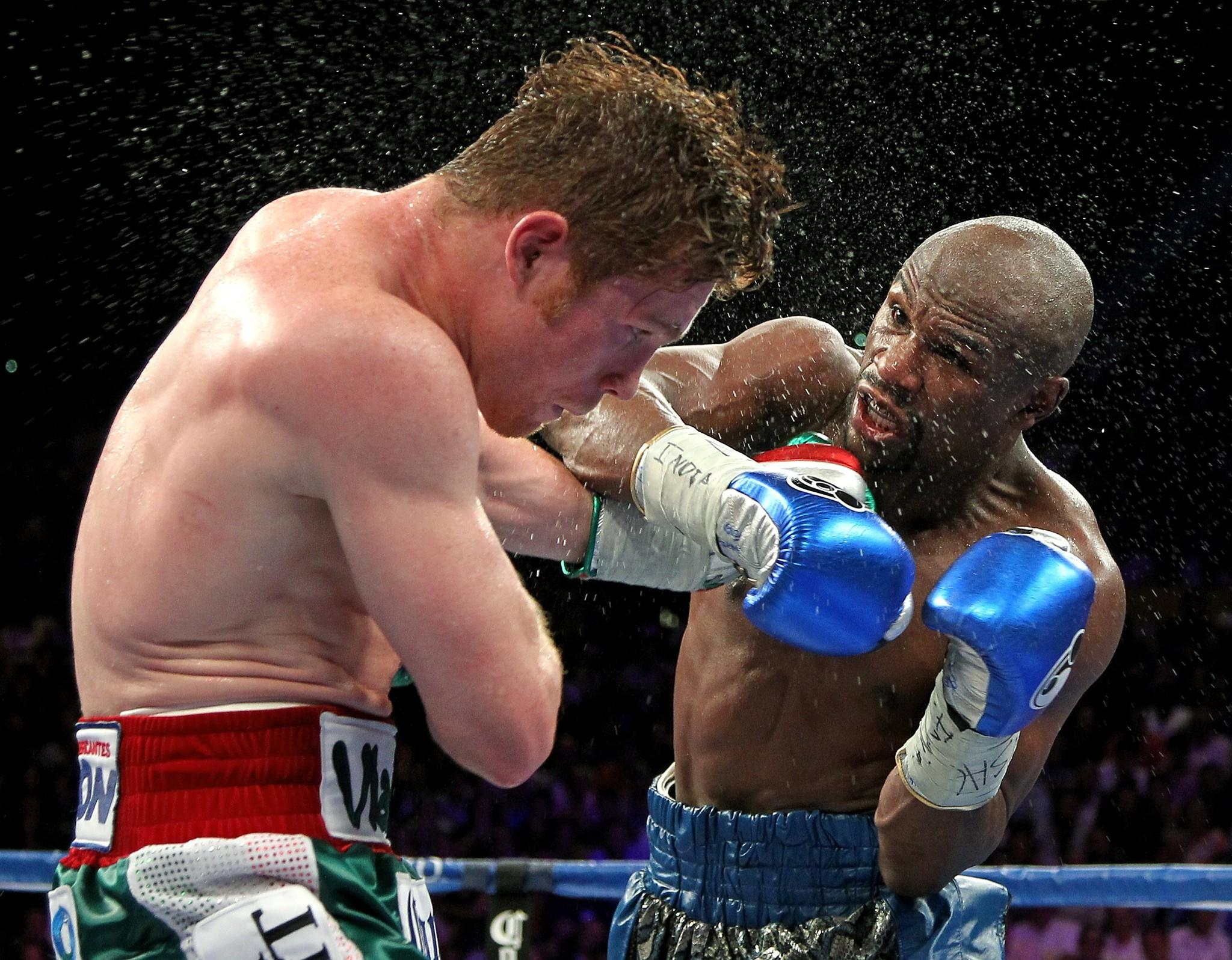 Boxers Floyd Mayweather Jr. of US (R) throws a left at Canelo Alvarez, Mexico, (L) during their WBC/WBA 154-pound title fight at the MGM Grand Garden Arena, September 14, 2013 in Las Vegas, Nevada. Mayweather won a majority decision. AFP PHOTO / John GURZINSKIJOHN GURZINSKI/AFP/Getty Images ORG XMIT: