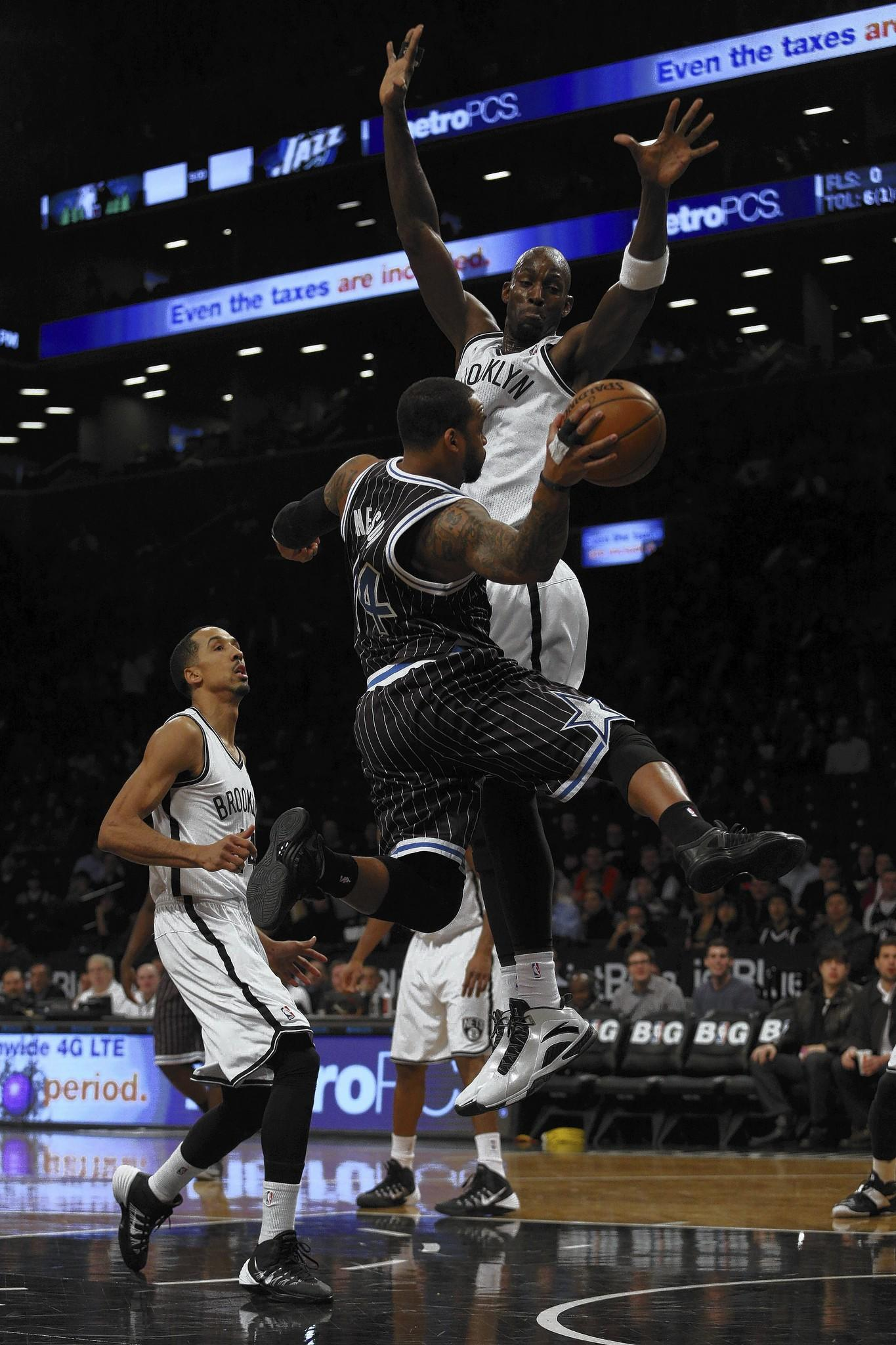 Orlando Magic point guard Jameer Nelson (14) passes the ball around Brooklyn Nets power forward Kevin Garnett (2) during the first quarter at Barclays Center.