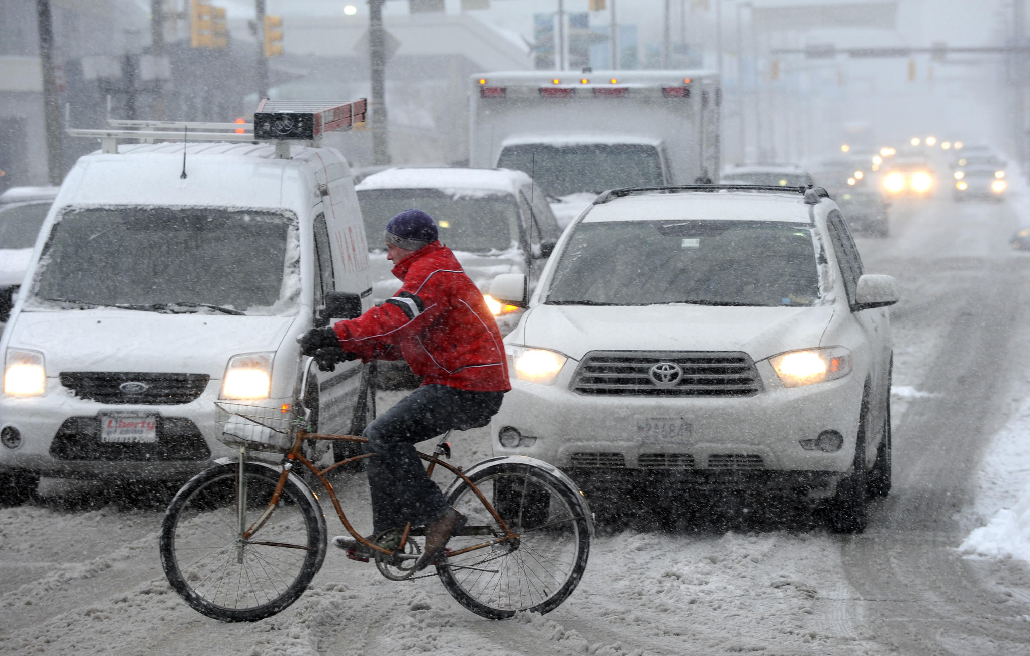 Ryan Weir, 29, rides his bike across Pratt St. at Calvert St. about 3:30pm on his way to Whole Foods to buy groceries. A snow storm covered the Inner Harbor and surrounding areas with several inches of snow.