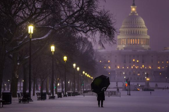 A visitor to the National Mall pauses in a late afternoon snowfall in Washington, D.C.