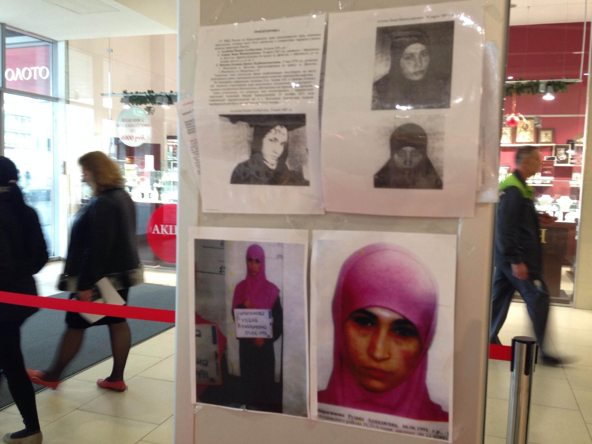 A picture taken on January 18, 2014, shows people walking past an information banner with the photos of police wanted suspected terrorists in a department store in the Russian Black Sea resort of Sochi. The sign under the colour photo (bottom R) reads: Ruzanna Ibragimova, born in 1991 in North Ossetia. Islamist insurgents based in North Caucasus republics such as Dagestan who are seeking their own independent state have vowed to disrupt the Sochi Games in order to undermine Russian President Vladimir Putin. AFP PHOTO / NINA ZOTINANINA ZOTINA/AFP/Getty Images ORG XMIT: -