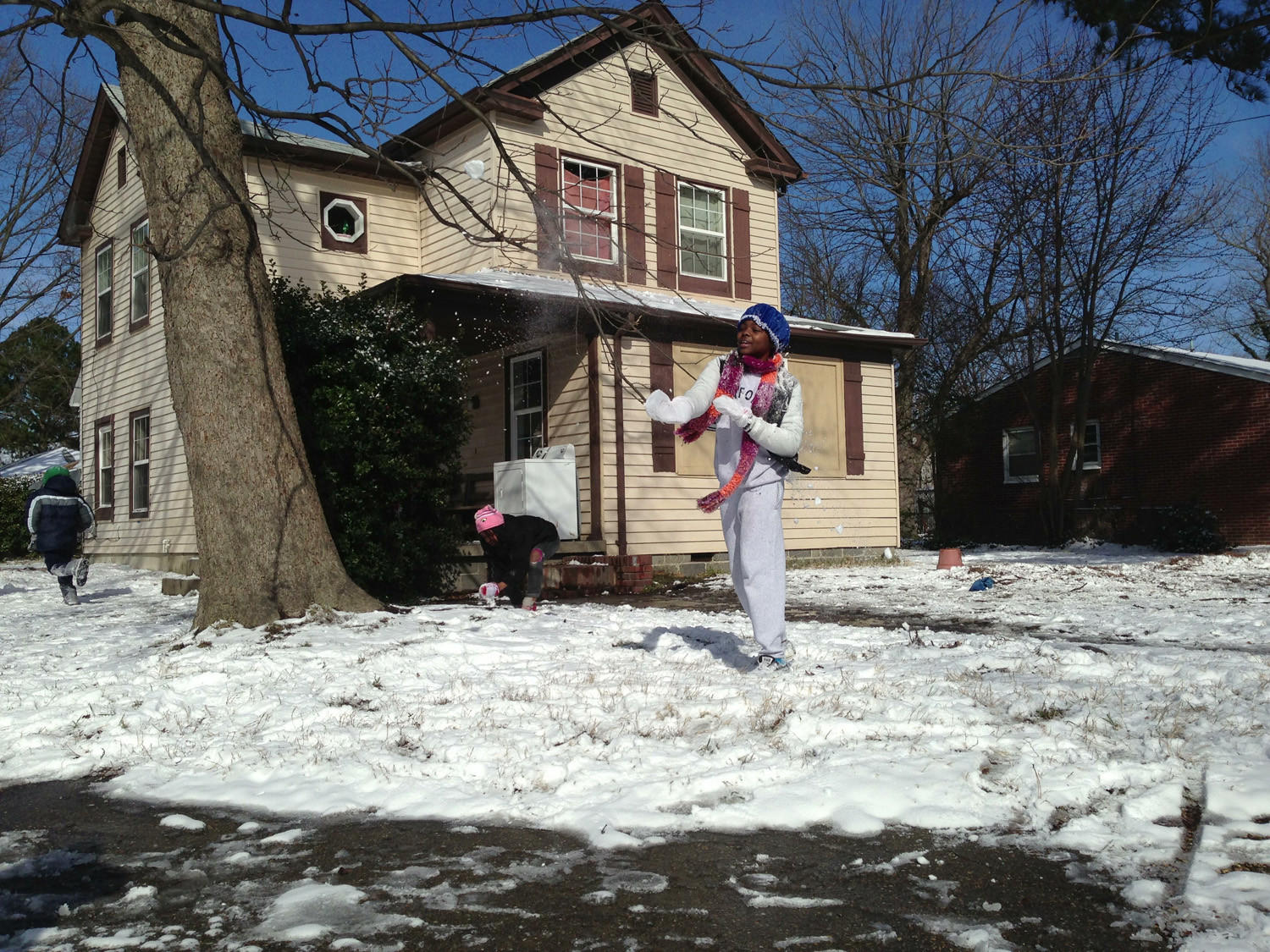 Hampton High School student China Armstrong, 15, throws snowballs with friends on a snow day Wednesday.