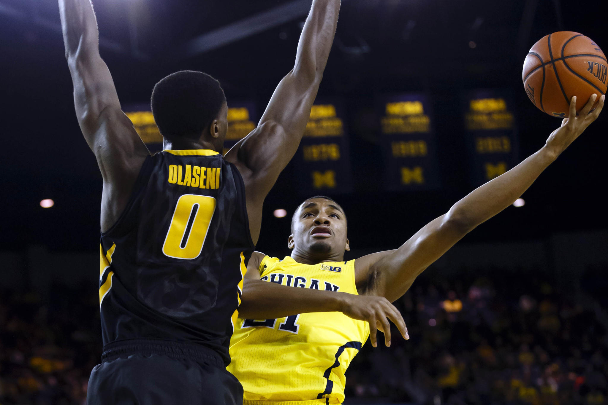 Michigan's Zak Irvin shoots on Iowa's Gabriel Olaseni in the first half at Crisler Arena.